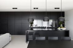 black kitchen stainless steel bench top and splashback. Black stained timber veneer cabinet cupboard doors. Simple black pendant over dining table.