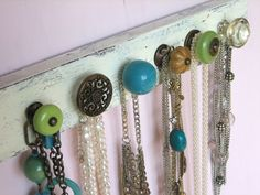 vintage jewelry hangs from vintage door knobs