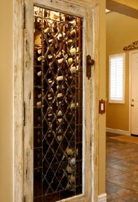 DIY Wine Cellar. Turn a small unused closet into a wine cellar. Install racks and change out the door. Beautiful.