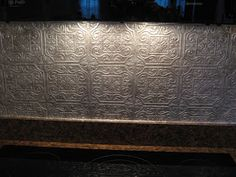 DIY: Faux Punched Tin Backsplash - using embossed wallpaper & metallic glaze.