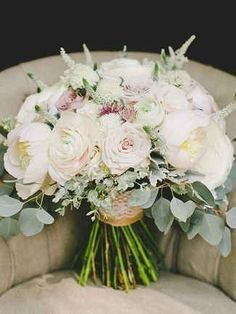 Bundle together white, blush, and mauve is classic flowers like garden roses, ranunculus, and peonies for a muted and earthy wedding bouquet.