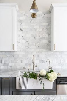 Two-toned gray and white cabinets, marble subway tile, Carrara countertops, a big farmhouse sink, and brass hardware give this kitchen a classic yet modern look. by lelia
