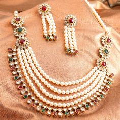 Sia Pearl Mala Necklace Set. A royal wedding necklace set with white moti pearls and Red & Green stones studded. This is perfect choice for your wedding jewellery needs.