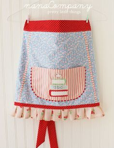 ***this apron is RESERVED for Annie, thank you!***    light blue, pink flowers, red accents...    and a little bird sitting on a pile of books.