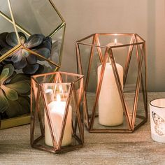 Copper and glass geometric candle holders. With  their glass triangles in a slim copper frame, these beautiful geometric  Copper Triangular Tea Light Holders radiate style. They would look  effortlessly stylish on a mantelpiece or a dining table.Made with iron  and glass. #ad