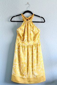 f200590fe3a Floral dress in a bright yellow and white color with a high beaded circle  neckline in
