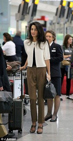 Journey: Mrs Clooney is pictured at Heathrow Airport in London yesterday as she got ready ...
