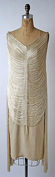 This evening dress is cut on the straight – rather unusual for Vionnet at that time. Made of oyster-white silk crepe, it is overlaid with a draped fringe that flows over the body and cascades down the side, giving a most alluring and chic touch