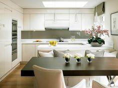 cuisine avec dosseret en verre gris et coin repas avec une table à manger et chaises