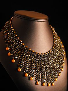 (BLACK AND GOLD EMBRACE (n) # 119) Individually strung Toho seed beads, with Czech faceted beads, freshwater pearls, and Swarovski crystals. It lays