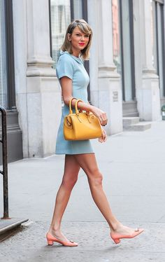 Taylor Swift wears a pastel blue mini dress with peach ballet flats and a yellow duffle bag