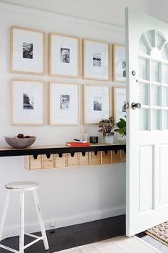 deco couloir avec sol en bois marron foncé, porte blanche, tableaux en cadres en bois clair, tabouret de bar en bois peint en blanc, tapis couleur crème près de la porte