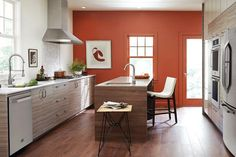 Textured and sleek kitchen with orange wall. Photo by Tim Nehotte.