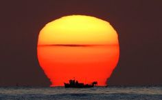 Whitley Bay, UK: A lobster catcher checks his pots as the sun rises over his small fishing boat in the North Sea