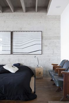 concrete wall with art over bed