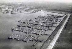 We zien hier een luchtfoto van de Waalhaven in het begin van de jaren '30. Rechts ligt het vliegveld.  Rij na rij rijgen de werkloze binnenvaartschepen zich aaneen. Linksboven liggen ook nog opgelegde zeeschepen, met de kap op de schoorsteen. Het was crisis....