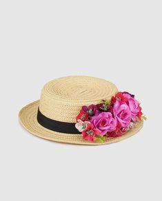 Sombrero tipo canotier tejido en color natural con flores en tonos rosas en un lateral y cinta negra.