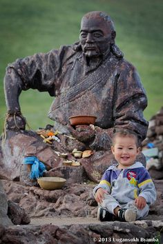 Little Mongolian boy sitting next to a statue of Toroi Bandi, the 'Robin Hood' of Mongolia, who had a habit of stealing the horses of the local Manchurian rulers, then eluding them by hiding near Shiliin Bogd Uul. The statue, dedicated in 1999, pointedly faces to China. Photo by Uugansukh Byamaba