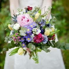 Very Pretty Bridal Bouquet Showcasing: Blue Eryngium Thistle, Blue Hyacinth, Pink Peonies, White Ranunculus, Yellow Tulips, Several Varieties Of Dianthus (Sweet William), Lavender/Yellow Asters, Baby Blue Eucalyptus & Several Additional Varieties Of Coordinating Florals & Foliage