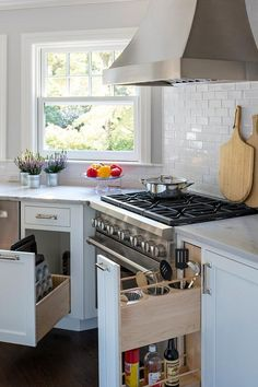 Gorgeous angled kitchen is equipped with a stainless steel French hood mounted beside a window above a stainless steel oven range fixed against white subway backsplash tiles.