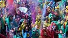 Partygoers throw multicoloured chalk dust over each other in central Dublin