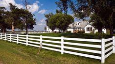 White rail fence surrounds tidy farmhouse in Kansas.
