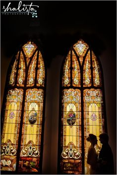 Dramatic bride and groom picture with stunning stained glass in the church.