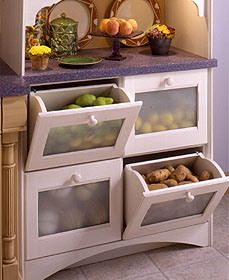 Tilt-out bins store fruits and vegetables in this kitchen by Columbia Cabinets.