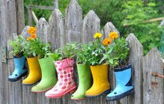 Hanging some colorful rainboot-turned-planters in a line