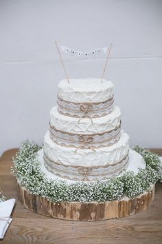 Rustic Wedding Cake on a wooden log with baby's breath. Hessian and lace on each tier. Tiers: Bottom tier - carrot cake; Second tier - lemon cake; Top tier - coffee cake.