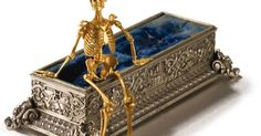 The fully articulated human skeleton in a velvet-lined coffin chased  around on each side with three panels showing the course of li...