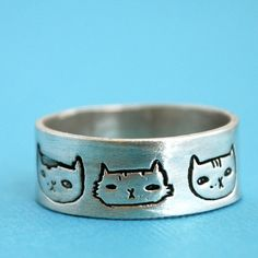 wide band CAT HEADS ring, illustrated by Gemma Correll, eco-friendly silver. Handcrafted by Chocolate and Steel (large). $66.00, via Etsy.