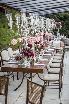 Mesa comunitária em tons de rosa. Mesa e cadeiras de madeira, candelabros de prata e cristal.  Vestida de Noiva | Blog de Casamento por Fernanda Floret | Blog de Casamento