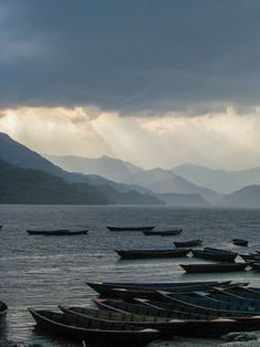 The storm clouds break and sunlight streams through onto Phewa Lake in Pokhara, Nepal.