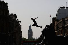 A Free Runner jumps from a Lion statue during the media launch of the Barclaycard World Freerun Championships at Trafalgar Square on 2 July, 2009 in London.
