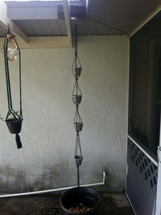 DIY Rain Chain. Took me a few weeks of engineering.  Finally decided to try macrame knots to hold the small pots. I had no gutter so I bought just the piece for the down spout and two end caps. Waterproof sealed, the used four 8ft lenghts of chain. Used a macrame square knot and notched the plastic pots for the chain to rest on.