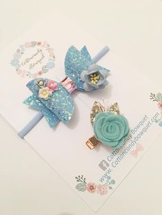Blue Glitter Hair Bow and Rose Hair Clip Set Blue glitter hair bow made with deluxe felt fabric and mulberry paper flowers. This bow is attached to a nylon headband. Also In this set is a single blue rose with gold glitter leaves attached to a rose gold crocodile clip. This bow