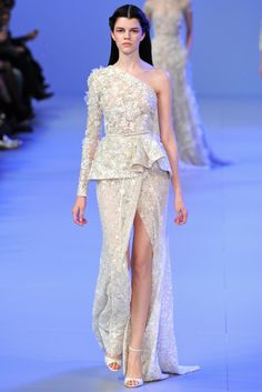 Elie Saab Spring 2014: This is a white one shoulder long sleeve gown with a peplum and a high front slit. The peplum adds interest and is unique. It is feminine and sexy!