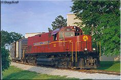Amid relatively tight clearances, A&M C420 #52 is seen here switching local industries in Rogers, Arkansas on May 14, 1999.