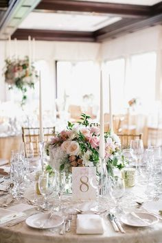 Romantic wedding table centrepiece with tall candles and fresh flowers
