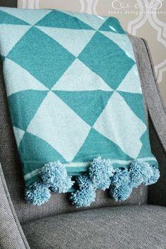 Put pom poms on a blanket.