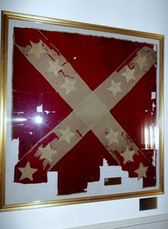 "Battle Flag of the 31st Virginia Infantry Regiment, C.S.A. Army of Northern Virginia. Made by the ladies of Beverly, home of Co. F, and presented to the regiment on May 5, 1862, by Gen T.J. ""Stonewall"" Jackson. The flag was in all of his battles except Chancellorsville. It was torn twice by shells, at Second Manassas and at Sharpsburg, where the color bearer, Sgt. ""Al"" Robinson was kiilled.  This flag was replaced by a newer, and 13 starred, battle flag for use at Fredericksburg and into…"