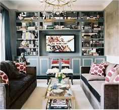 2. Flank It. Bookcases both skinny and wide enclose a television and visually frame it with their vertical placement. Flanking a television with free standing or built in bookcases and surrounding it with decorative objects balances the weight of the big screen and reduces the television's dominance in a living space.