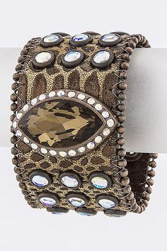 """This cuff is 100% genuine leather decorated with rhinestones and studs throughout. There is an oval-shaped embellishment in the middle decorated in crystals studs. The leather cuff has a snap button closure. Length: 8"""" - Width: 2"""" $59.99"""