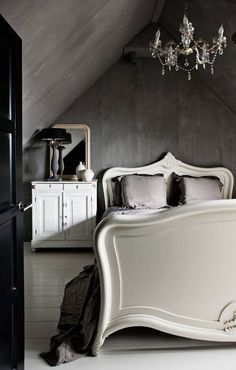 deep concrete grey industrially inspired walls paired with a classically feminine bed, crystal chandelier and black door.