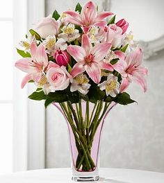 """Pink roses, tulips and Asiatic Lilies combine with white Peruvian Lilies and lush greens, arranged to perfection in a designer pale pink glass vase, to create a bouquet that showers your special recipient with elegance and grace.  Approximately 21""""H x 16""""W"""