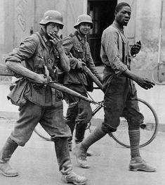 Deutsche Soldaten mit einem gefangenen französischen Soldaten eines Kolonialregiments ab., 1940 - pin by Paolo Marzioli