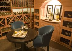 Light wood makes up the custom storage cabinets which include a round wine table paired with blue upholstered chairs.