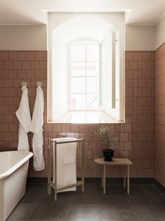 Bathrooms are finished with vintage pink square tiles and Iföbath fixtures.