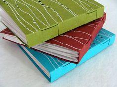 Collection Bulle by Julie Auzillon.   Petite série de carnets    reliure à couture invisible, réalisée sans collage, format 11x11 cm    décor en papier recyclé perforé et strié à l'encre blanche    chaque exemplaire est différent    2011